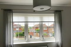 Braided semi sheer roller blind with coloured voile dress curtains and brushed stainless steel pole