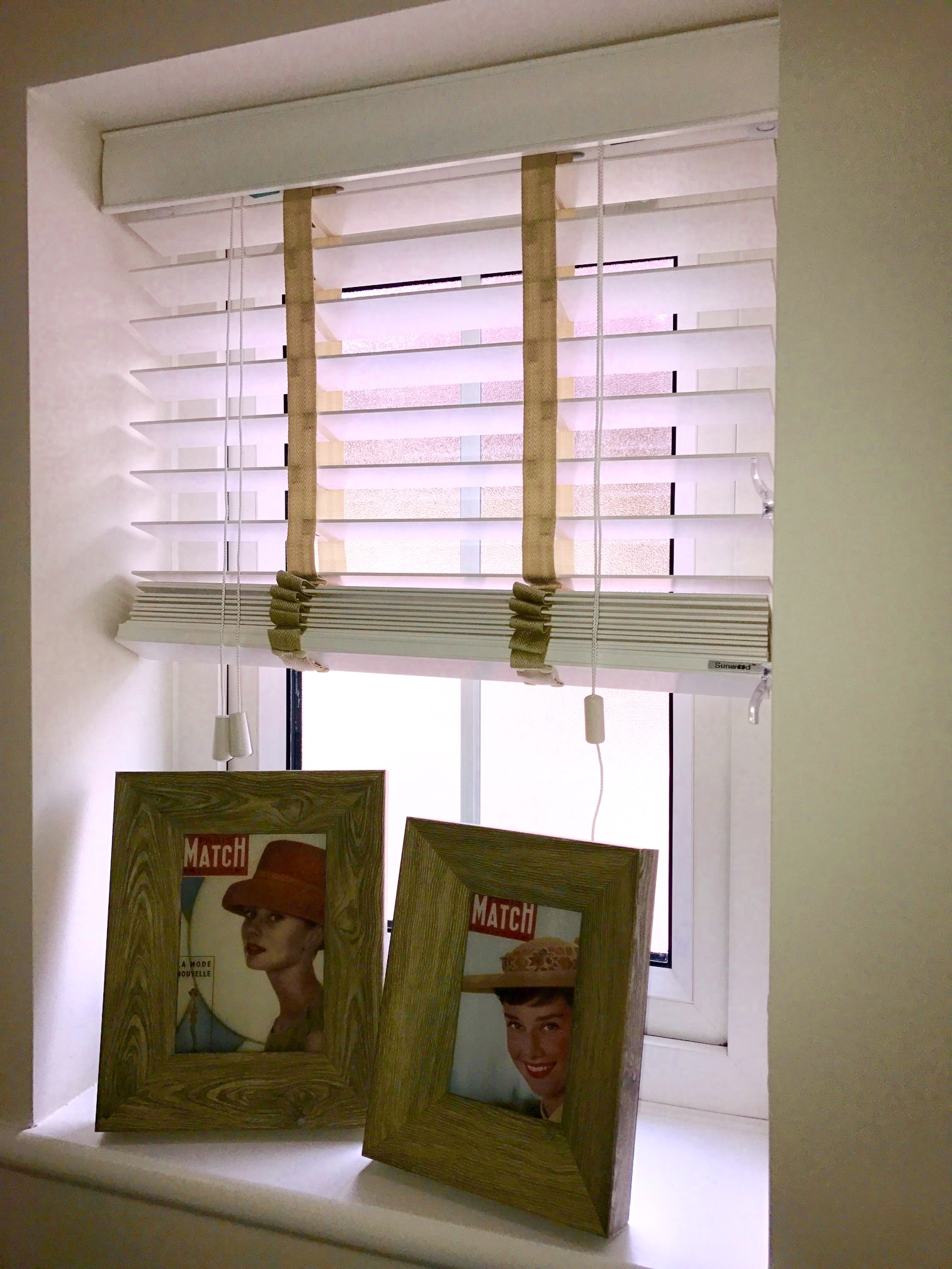 Two picture frames on a window sill