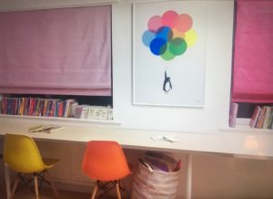 Childrens room with pink blinds and a painting