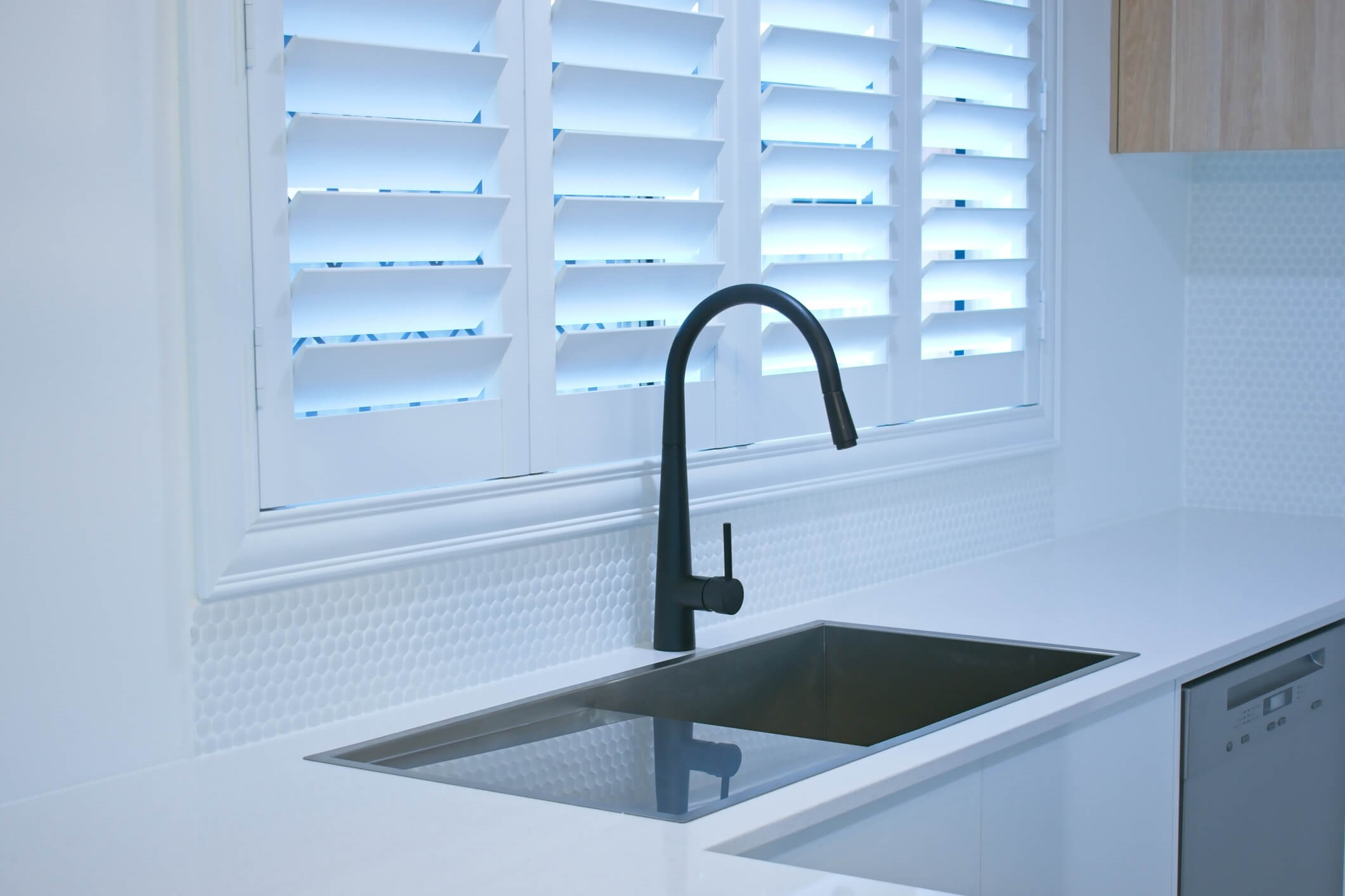 white window shutters with black tap in kitchen