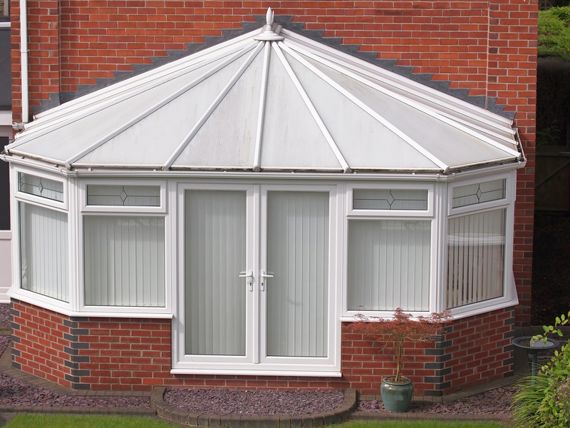 white conservatory outside the rear of the house, with blinds